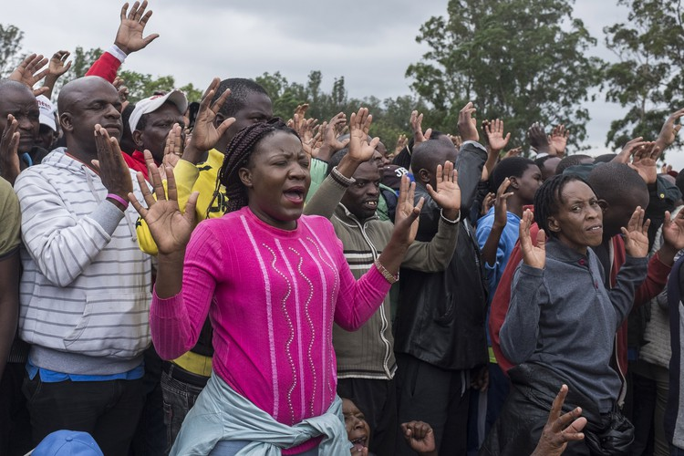 People raise their hands in prayer at the Zimbabwe Grounds.
