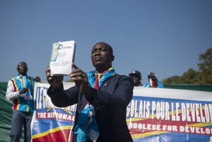 Photo of man holding up DRC constitution