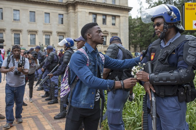 Photo of student protester handing flowers to police officer.