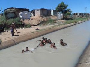 Photo of children swimming in canal