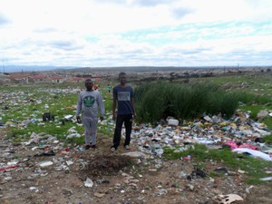 Photo of two men in a littered field