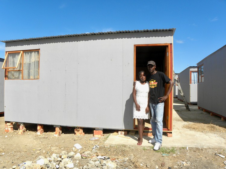 Photo of two people in front of a temporary house