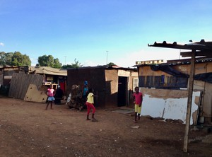 Photo of some kids and behind them shacks