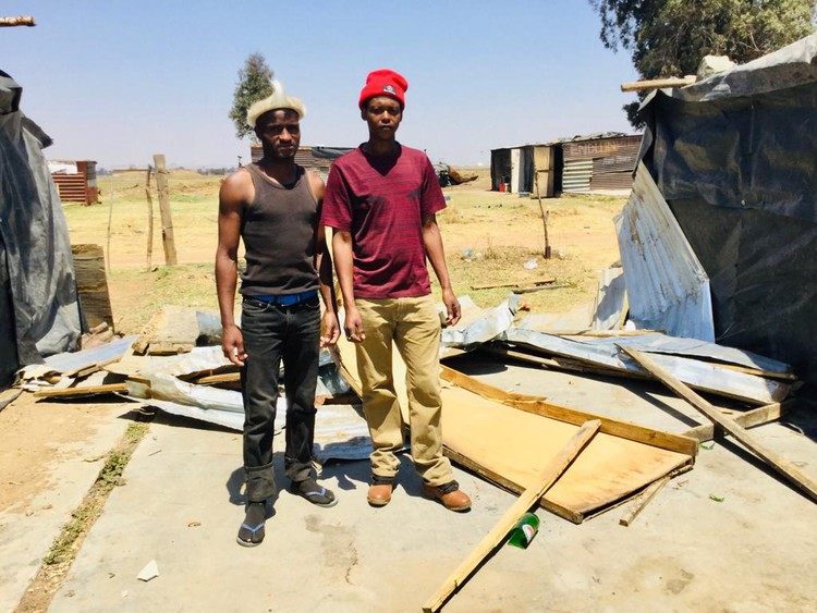 Photo of two men in front of a demolished shack