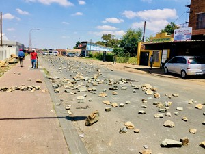 Photo of a street strewn with rocks