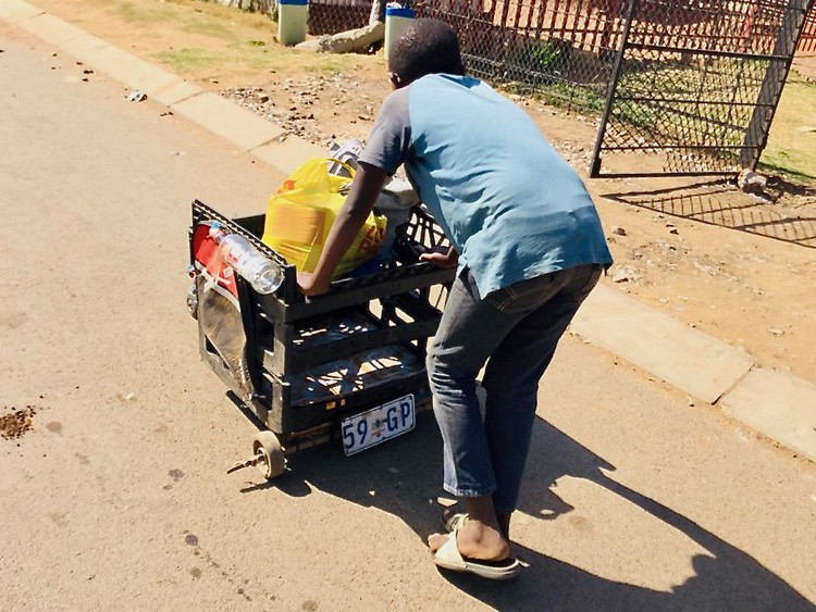 Photo of a boy pushing a makeshift trolley