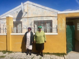 Photo of two people outside a house