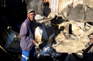 Photo of a man and a burnt out shack