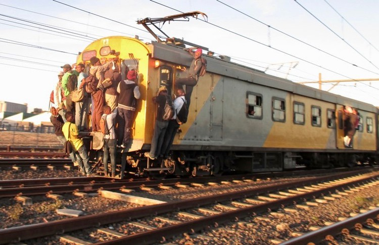 Photo of people clinging onto train