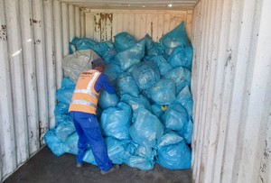 Photo of a man inside a rubbish container