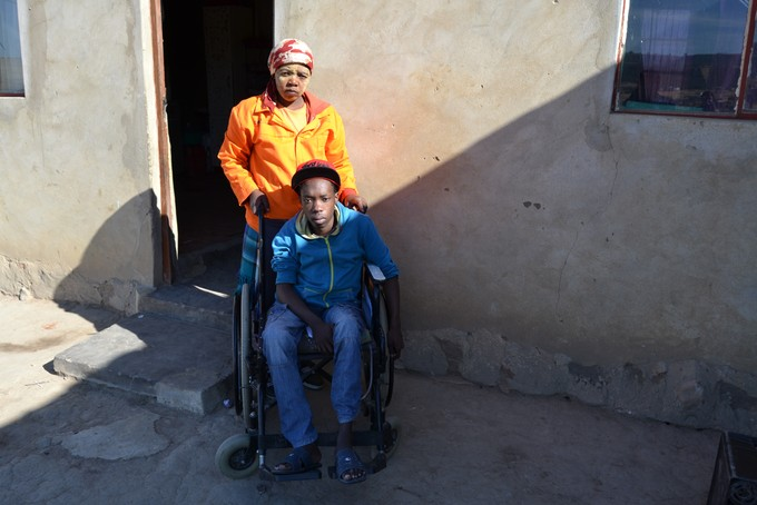 Photo of Montoedi Nyangweni in a wheelchair, with his mother Nokukhuthala
