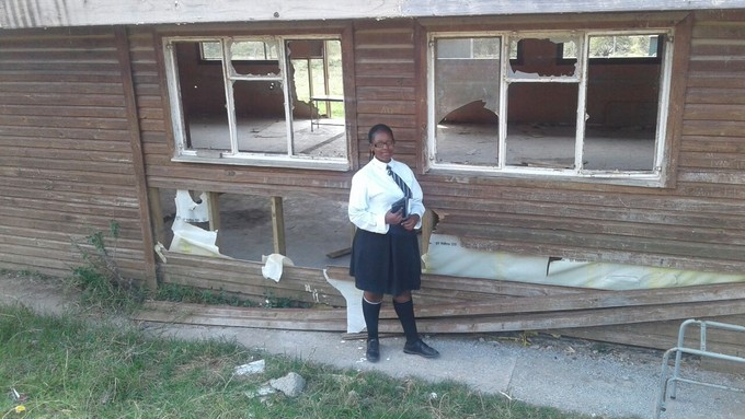 Photo of student outside dilapidated school