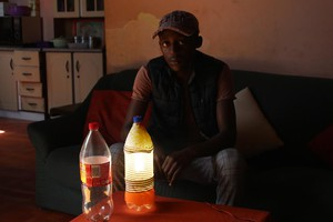 Photo of man with lamp made out of bottle