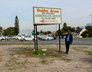 Photo of a man and a sign for Golden Arrow