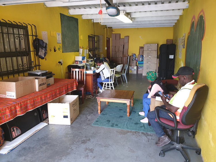 Photo of people at desks in a garage