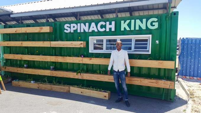 Photo of a man infront of a shipping container made into a shop