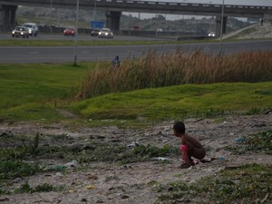 Photo of boy quite far from camera defecating with cars driving by on the N2