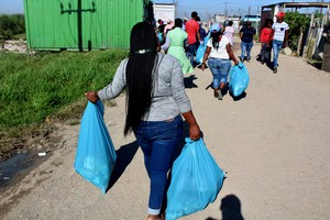 Photo of people carrying refuse bags