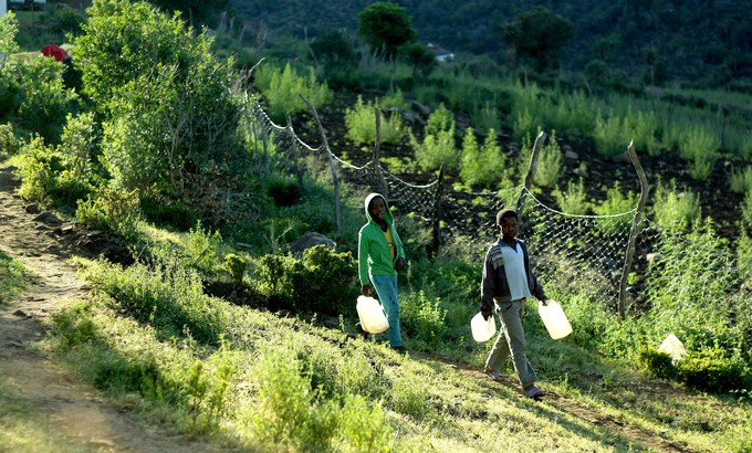 Ongezile (green jacket) and Siya walk down the hill with empty buckets.