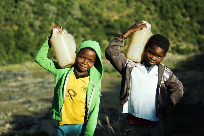 Photo of two boys carrying water