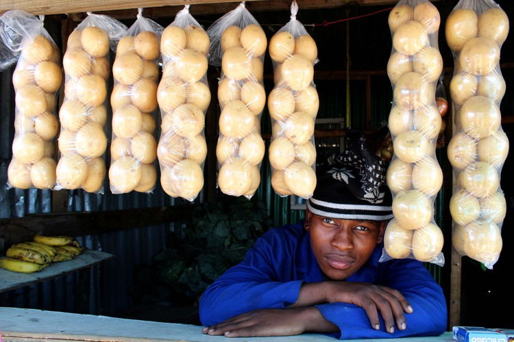 Thabiso Tshepe sells fruit and vegetables at his brother's stand.