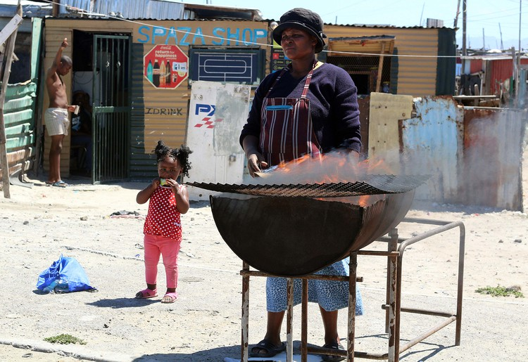 Nomfuneko Sitwayi braais and sell chicken feet (with help from young Ndalo Sitwayi).