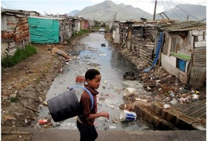 Photo of boy walking past canal in Masiphumelele.
