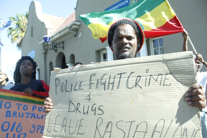 Photo of a Rastafarian man protesting outside Woodstock Police Station.