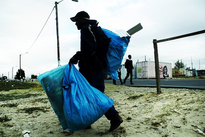 Photo of Plaatjies carrying bags of scrap in the evening.