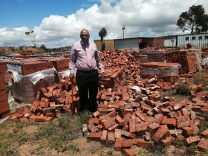 Photo of man with pile of bricks
