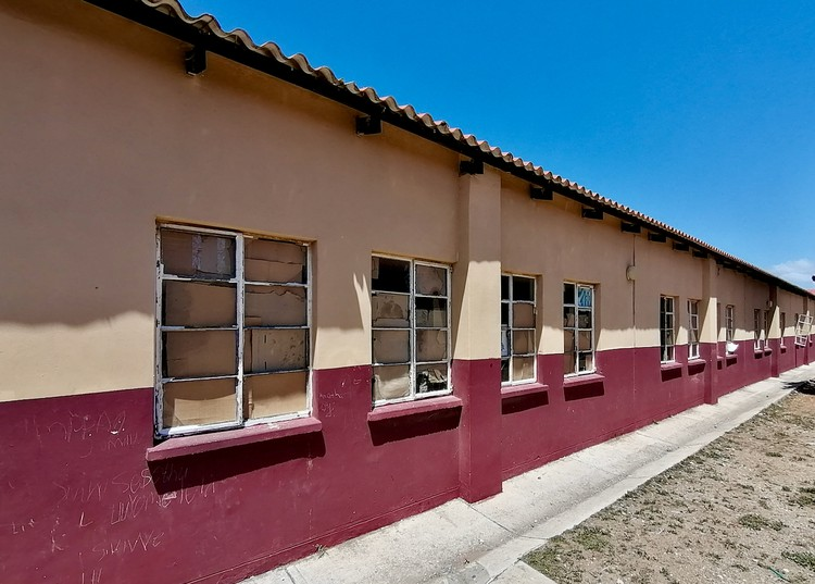 Photo of school building with broken windows
