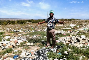 Photo of a man standing in a field of rubbish