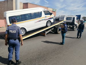 Photo of a taxi being loaded  on to a flatbed truck