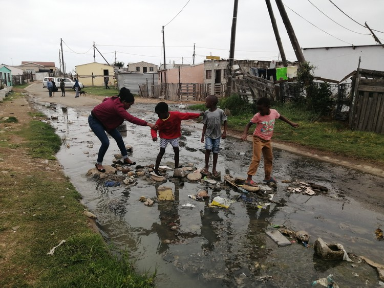 Photo of people crossing stream of sewage
