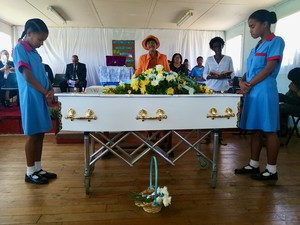Photo of a coffin and mourners