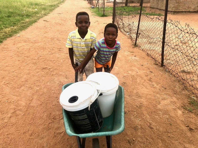 Photo of two children with buckets