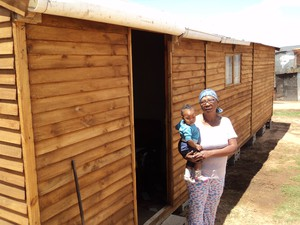 Photo of woman and her grandchild outside home