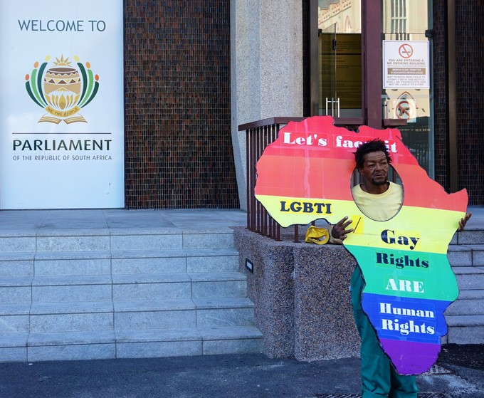 Photo of a man infront of parliament with a gay rights poster