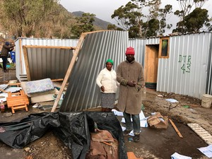 Photo of two people in front of blown-down shack