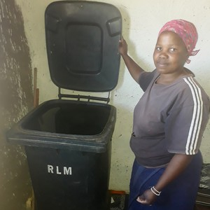 Photo of a woman holding up the lid of a black bin