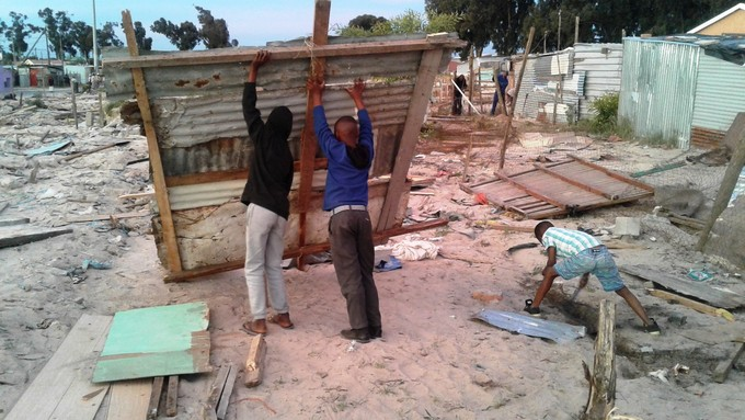 Photo of people building shacks