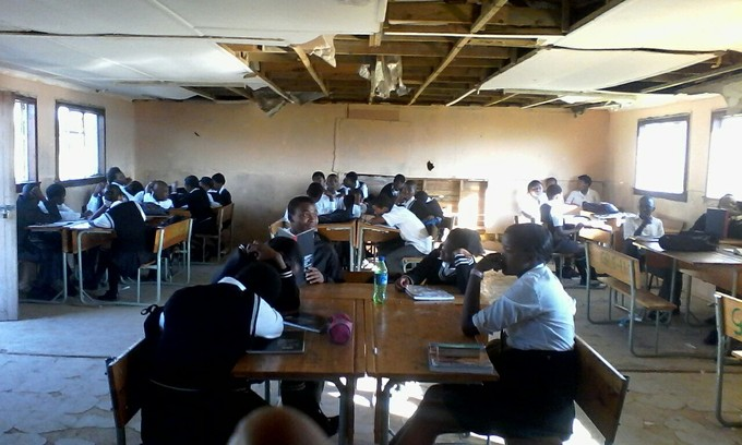 Photo of students in a classroom with a broken ceiling