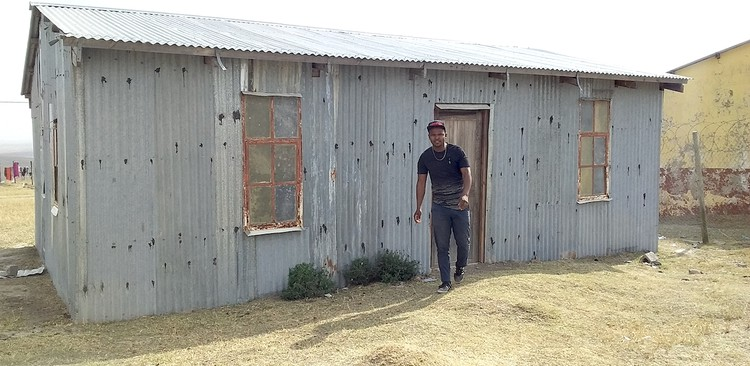 Photo of a shack and a man in front