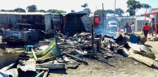 Photo of a burnt shack and bakkie
