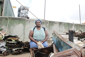 Photo of a woman sitting next to scrap metal