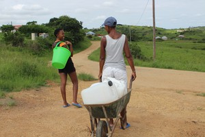 Photo of women pushing a wheelbarrow with containers to fetch water