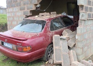 Photo of car broken through house wall
