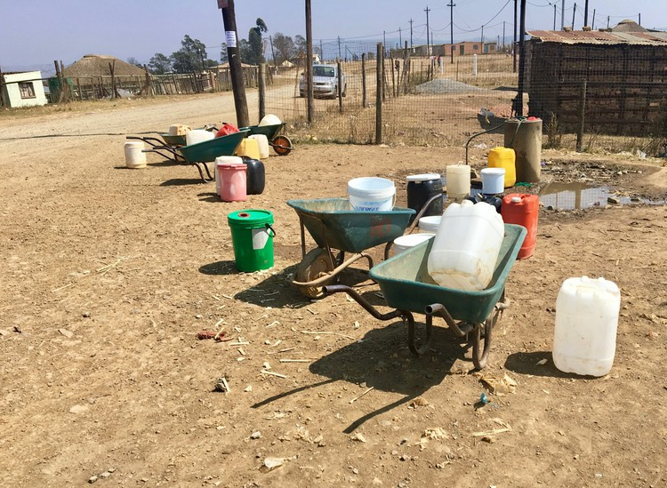 Photo of wheeelbarrows and plastic water containers