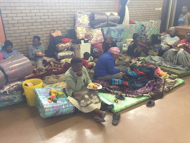 Photo of resdents sitting with their belongings in the community hall