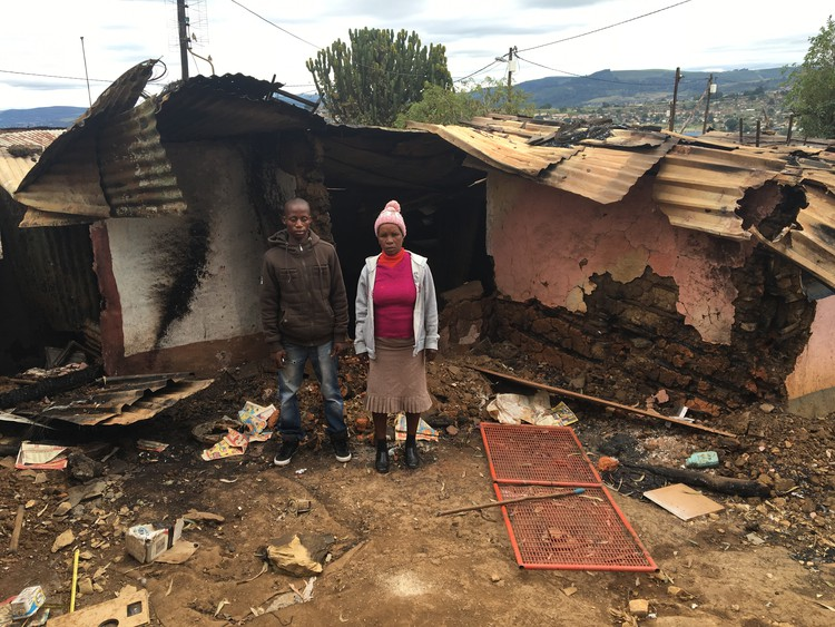 Photo of two people in front of burned house